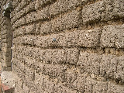 Adobe is sun-baked clay with straw added as a stabilizer.  It lasts a long time, and doesn't pollute the eviroment like brickmaking does (they burn tires in the brick-baking ovens).  It's less stable in earthquakes and floods, though.