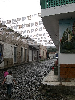 Cobblestone streets.  The cut paper streamers are left over from a religious procession.  Nowadays they are made of plastic.