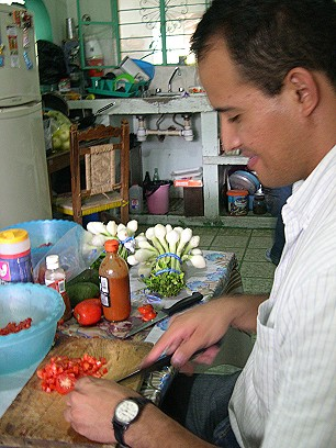 As the coals heat up, Omar chops tomatoes for a salsa