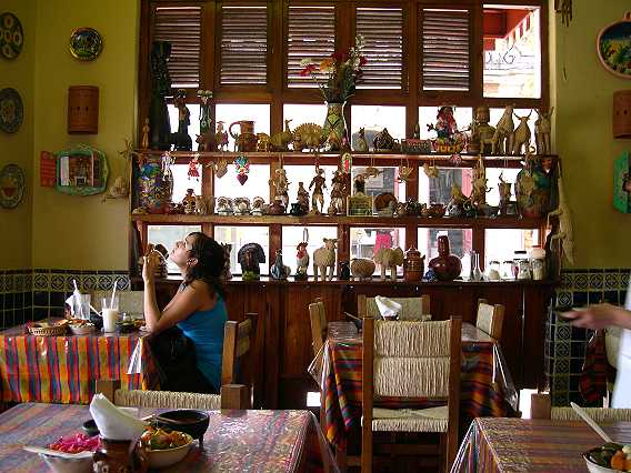 """We order and sit back to enjoy the decor.  The young lady doesn't have a crick in her neck.  She is reading one of the many, many plates painted with local sayings, like """"It's better to be fat and feliz (happy) than thin and amarga (bitter).""""  We really like that one."""