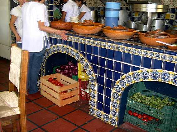 Fresh vegetables are stored under the cement and tile counter.  The green veggies are jitomate verde--tomatillos--that are used to make an incredible sauce.  Here they are before husking.  Each fruit is covered with a dry, papery husk like a Chinese lantern.