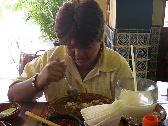 Just as the beans are gone, we are served our birria.  They only serve two or three different things here, so they are very speedy.  Imelda starts right in.  She is drinking horchata, a refreshing drink made from mashed rice and sugar.