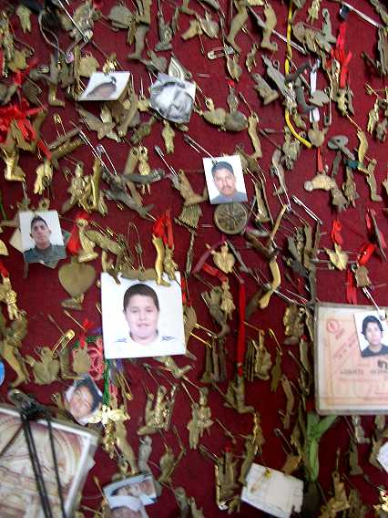 The photos are of people who are sick or missing. The charms are offerings--a heart for heart attacks or love, a leg for knee and leg problems, etc. The charms are available outside the basilica.