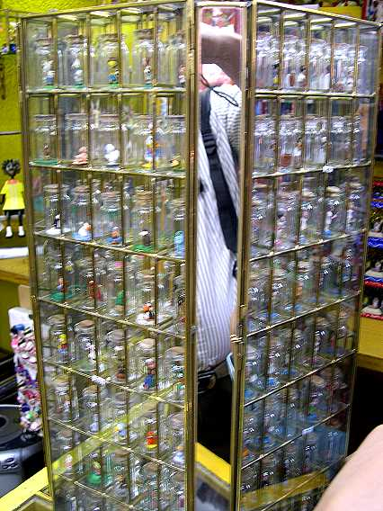 Clay characters in glass bottles, each about an inch and a half tall. There are 150 different ones in this tower--and there are two towers.