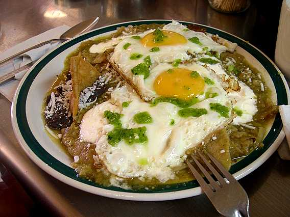 Chilaquiles.  This is Mexico.  This is what I miss when I'm in New York.  Chilaquiles are strips of tortillas, deep fried, and then covered with green tomatillo/chile sauce and cream, and montado with a huevo estrellado (sunny-side up egg).  Served with refried black beans and sprinkling of cotija cheese and drops of green chile sauce, this is heaven on a plate.  With a large orange or carrot juice and hard rolls, breakfast runs $4 dollars and fuels you for days.