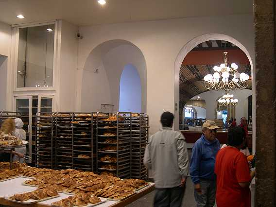 On the left is the glass elevator--not for riders, but to transport pastries from above.  They may come all the way down from heaven, as far as we are concerned.  The racks full of pastries gives some idea of the amount of business done here.
